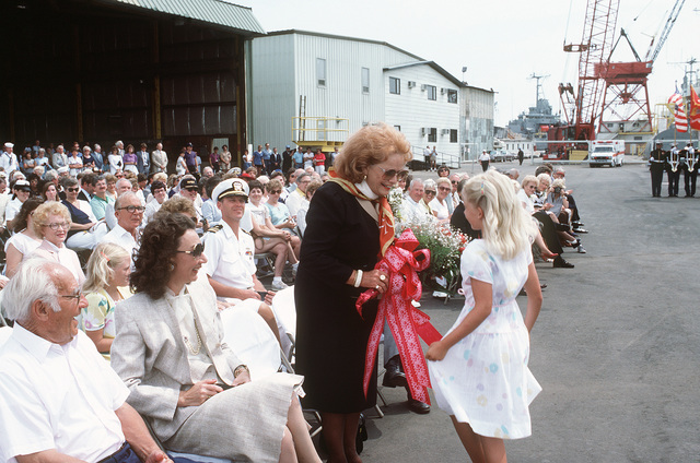 A girl presents Mrs. Dornell Kilcline, sponsor, with a bouquet of flowers during the commissioning ceremony for the salvage ship USS SAFEGUARD (ARS 50)