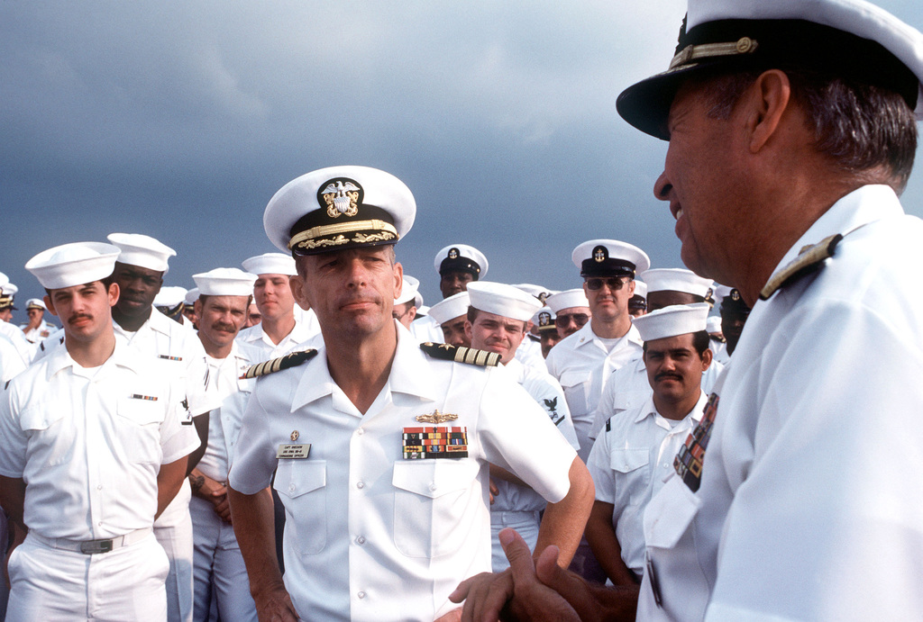 Captain Gerald E. Gneckow, Commanding Officer of the battleship USS IOWA (BB 61), center, listens to Admiral Wesley McDonald, Commander in CHIEF, United States Atlantic Fleet; as he presents the 1984 Batterberg Cup to Gneckow and the IOWA. The award is presented for overall excellence among Surface Fleet Atlantic vessels