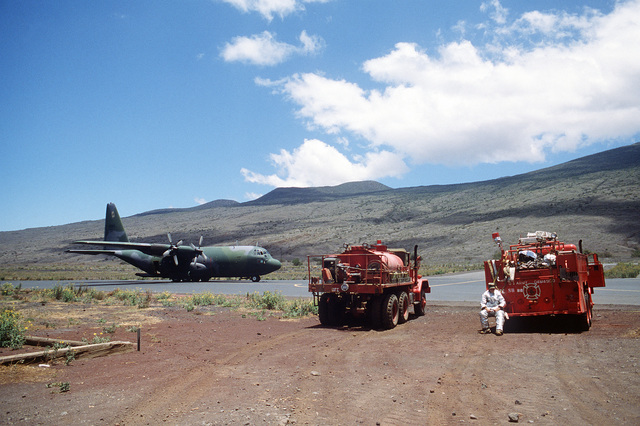 A C-130B Hercules aircraft from the 757th Tactical Airlift Squadron, 910th Tactical Airlift Group, Air Force Reserve, is parked on the runway during a joint airborne/air transportability training exercise. Standing by in the foreground are a water truck and a fire truck