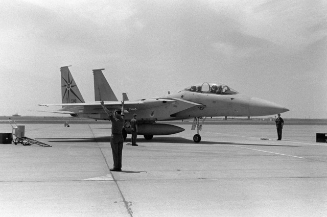 An F-15B Eagle aircraft prepares for a mission during the 12th Air Force Gunsmoke '85 competition. A plane director signals to aircraft on the flight line in the foreground