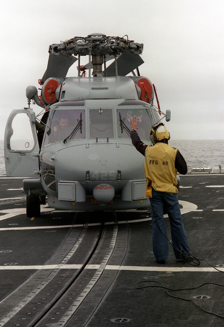 A crew member gives hand signals as an SH-60B Sea Hawk helicopter is pulled into a hangar by the recovery assist secure and traversing (RAST) system aboard the guided missile frigate USS HALYBURTON (FFG-40). The ship is participating in exercise Ocean Safari '85