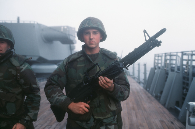 A Marine aboard the battleship USS IOWA (BB 61), armed with an M60 machine gun, participate in a self defense force test during Exercise OCEAN SAFARI '85