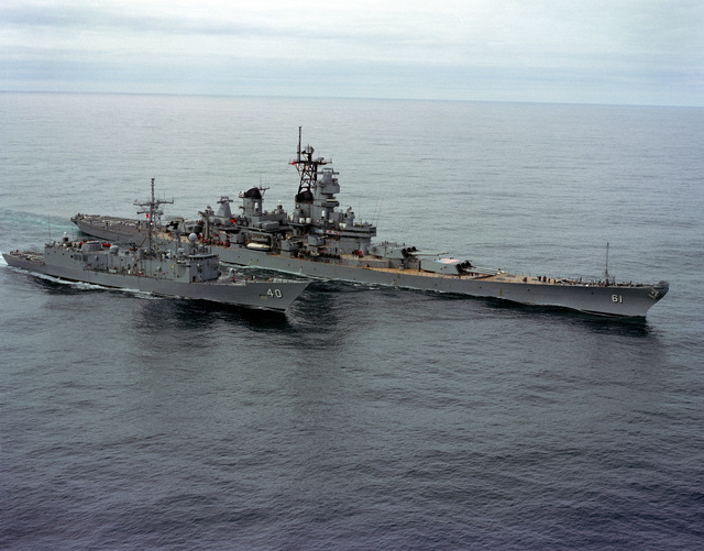 A starboard bow view of the battleship USS IOWA (BB 61) refueling the guided missile frigate USS HALYBURTON (FFG 40) during NATO Exercise OCEAN SAFARI '85