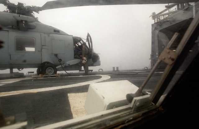 A view from the recovery assist secure and traversing (RAST) control station as an SH-60B Sea Hawk helicopter is secured for stowage in a hangar aboard the guided missile frigate USS HALYBURTON (FFG-40). The ship is participating in exercise Ocean Safari '85