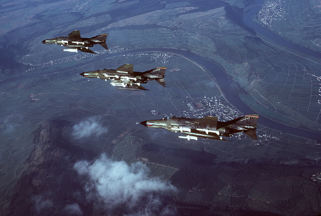 Air-to-air left side view of two F-4E Phantom II and an F-4G Phantom II Advanced Wild Weasel fighter aircraft (upper left) from the 52nd Tactical Fighter Wing, Spangdahlem Air Base, Germany. The aircraft, flying over the Mosel River in banked formation, are armed with an AGM-78 Standard anti-radiation missile (F-4G), AGM-45 Shrike air-to-surface missiles, AIM-7 Sparrow III and AIM-9 Sidewinder air-to-air missiles. The aircraft are equipped with electronic countermeasures pods