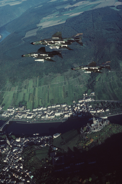 "Air-to-air underside view of an F-4G Phantom II Advanced Wild Weasel fighter aircraft leading two F-4E Phantom II fighter aircraft from the 52nd Tactical Fighter Wing, Spangdahlem Air Base, Germany. Banking right in ""V"" formation, the aircraft are armed with an AGM-78 Standard anti-radiation missile (F-4G), AGM-45 Shrike air-to-surface missiles, AIM-7 Sparrow III and AIM-9 Sidewinder air-to-air missiles and are equipped with electronic countermeasures (ECM) pods"