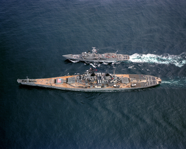 An aerial port beam view of the battleship USS IOWA (BB 61) refueling the guided missile frigate USS HALYBURTON (FFG 40) during NATO Exercise OCEAN SAFARI '85