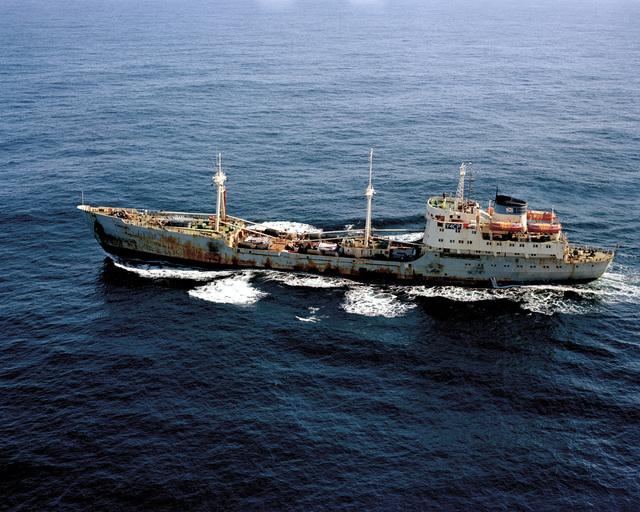 An aerial port view of the Romanian cargo ship SS EVERSHAGEN underway near the battleship USS IOWA (BB 61) during NATO Exercise OCEAN SAFARI '85