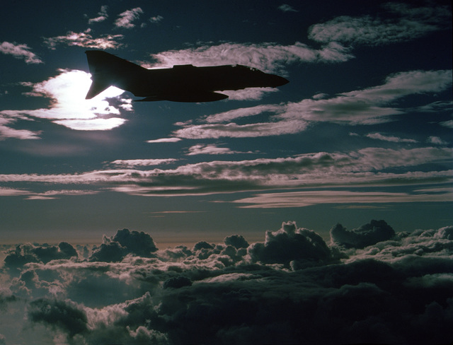 An air-to-air silhouetted view of a Marine Strike Figher Squadron 333 (VMFA-333) F-4 Phantom II aircraft