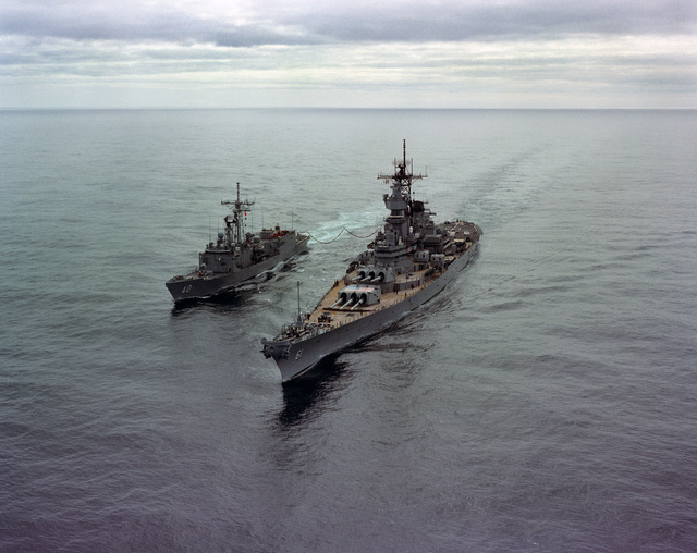 An elevated port bow view of the battleship USS IOWA (BB 61) refueling the guided missile frigate USS HALYBURTON (FFG 40) during NATO Exercise OCEAN SAFARI '85