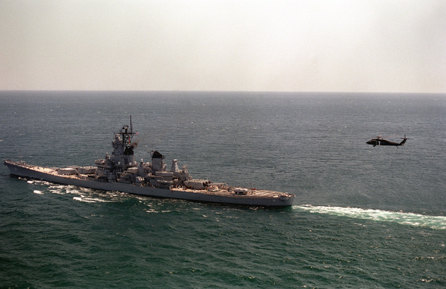 An elevated port quarter view of the battleship USS IOWA (BB-61) underway during exercise Ocean Safari '85. An SH-60B Sea Hawk helicopter approaches the stern of the ship
