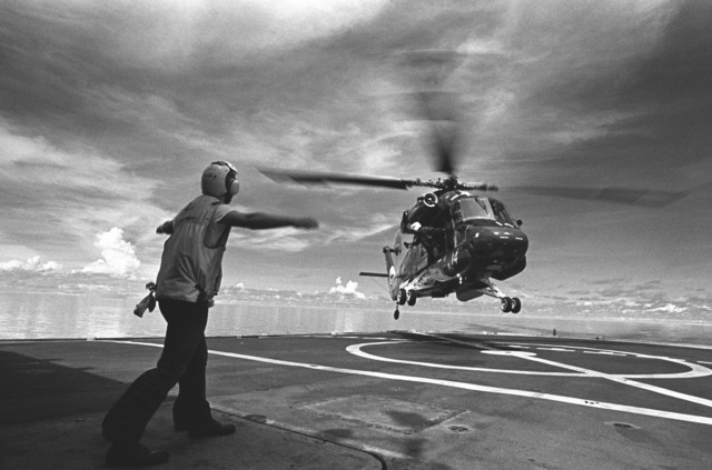 Aviation Machinist's Mate 3rd Class (AD3) Jeffrey C. Bell signals to an HH-2D Seasprite helicopter landing aboard the surveying ship USNS CHAUVENET (T-AGS 29). The helicopter is assigned to Helicopter Light Antisubmarine Squadron 31 (HSL-31), Detachment B