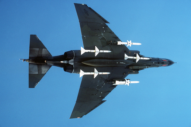 Bottom view of an F-4E Phantom II fighter aircraft assigned to the 52nd Tactical Fighter Wing, Spangdahlem Air Base, Germany, in flight. Mounted on the front of the wings are two AGM-45A Shrike air-to-surface missiles; mounted towards the centerline of the aircraft are AIM-7 Sparrow III air-to-air missiles. The aircraft is equipped with electronic countermeasures (ECM) pods