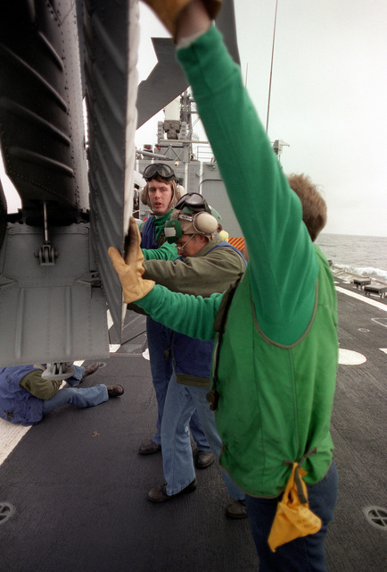 Crew members fold the tail section of an SH-60B Sea Hawk while the helicopter is being prepared for stowage in a hangar aboard the guided missile frigate USS HALYBURTON (FFG-40). The ship is participating in exercise Ocean Safari '85