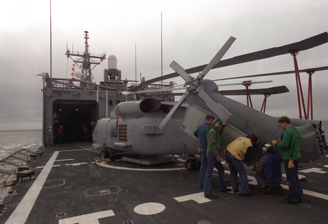 Crew members lock the tail section of an SH-60B Sea Hawk in a folded position prior to moving the helicopter into a hangar aboard the guided missile frigate USS HALYBURTON (FFG-40). The ship is participating in exercise Ocean Safari '85