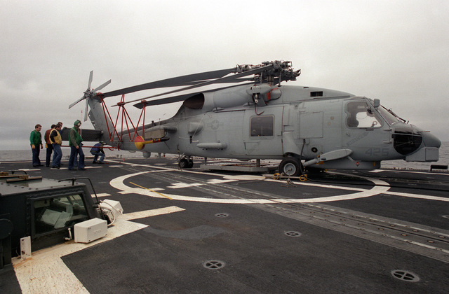 Crew members prepare an SH-60B Sea Hawk helicopter for hangar stowage aboard the guided missile frigate USS HALYBURTON (FFG-40). The ship is participating in exercise Ocean Safari '85
