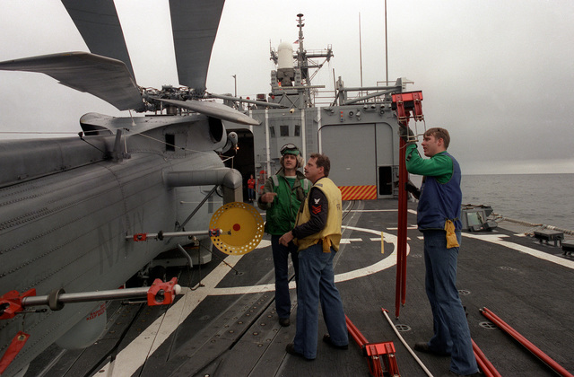 Crew members prepare to attach rotor supports to an SH-60B Sea Hawk helicopter as it is prepared for hangar stowage aboard the guided missile frigate USS HALYBURTON (FFG-40). The ship is participating in exercise Ocean Safari '85