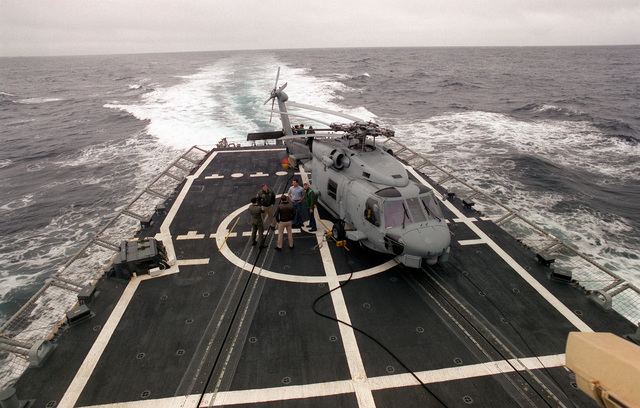 Crew members stand by to secure SH-60B Sea Hawk helicopter on the fantail of the guided missile frigate USS HALYBURTON (FFG-40) during exercise Ocean Safari '85