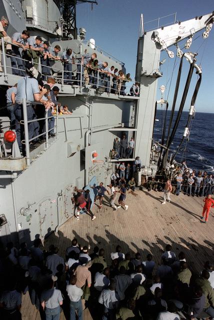 Crewmen aboard the battleship USS IOWA (BB-61) play basketball as others watch during exercise Ocean Safari '85