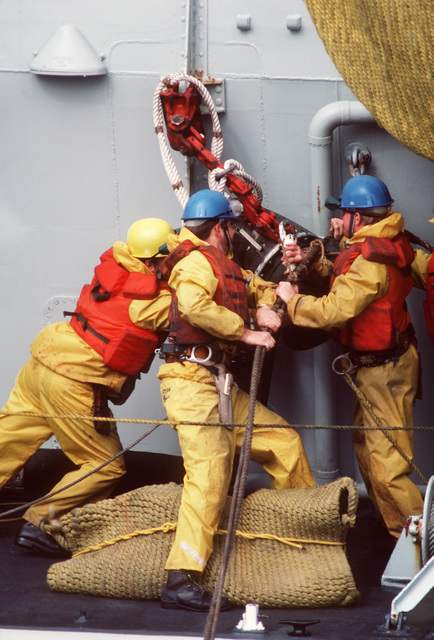 Crewmen from the Canadian frigate HMCS NIPAGON (F 266) prepare for refueling by the battleship USS IOWA (BB 61) during NATO Exercise OCEAN SAFARI '85