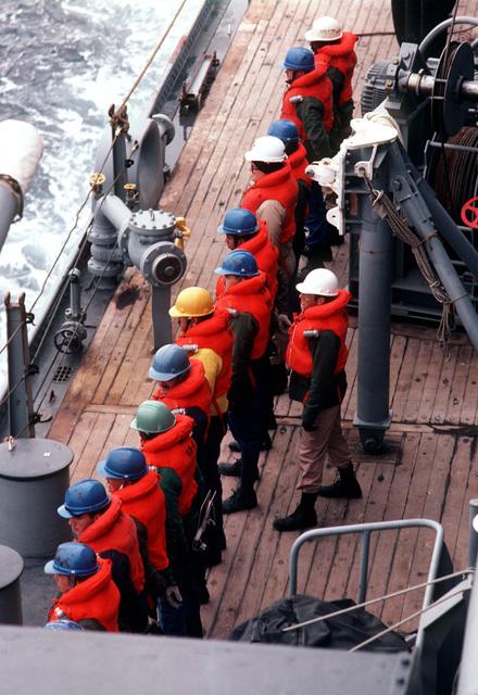 Crewmen wearing life jackets prepare for underway replenishment aboard the battleship USS IOWA (BB 61) during NATO Exercise OCEAN SAFARI '85