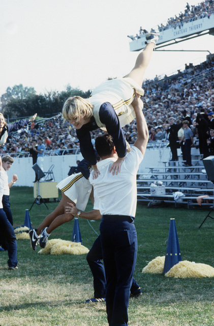 Members of the US Naval Academy cheerleading squad perform at a football game at the Navy-Marine Corps Memorial Stadium