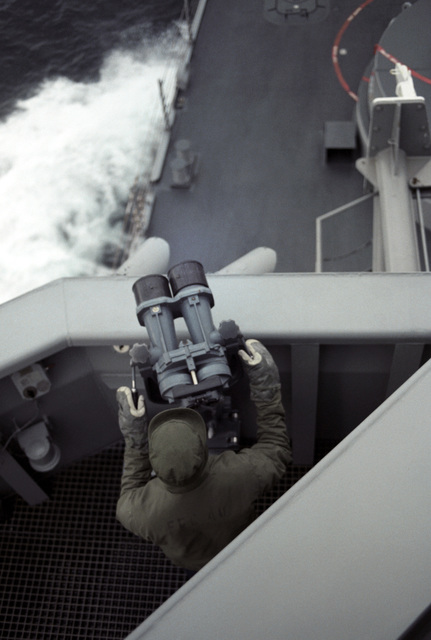 North Atlantic. A crew member aboard the guided missile frigate USS HALYBURTON (FFG 40) operates a pair of high power binoculars during Exercise OCEAN SAFARI '85