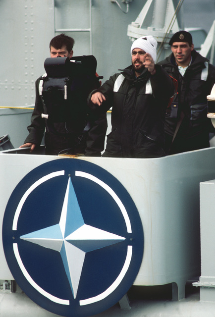 Signalmen aboard the Canadian frigate HMCS NIPAGON (F 266) participate in NATO Exercise OCEAN SAFARI '85. The shield indicates that the NIPAGON is a unit of the Standing Naval Force Atlantic