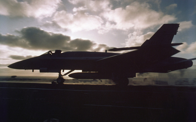 Silhouetted left side view of an F-14 Tomcat fighter aircraft preparing for takeoff from the Kitty Hawk class aircraft carrier USS CONSTELLATION (CV-64)