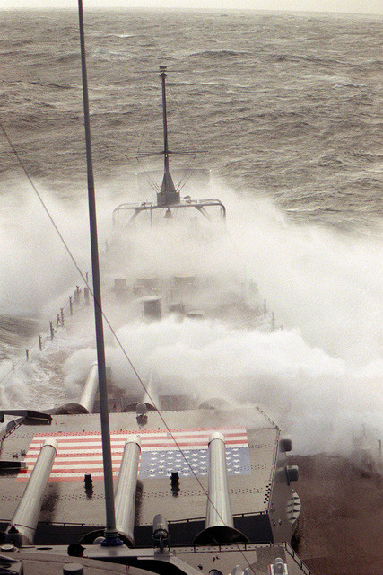 The battleship USS IOWA (BB-61) takes water over the bow while underway in heavy seas during Operation Safari '85