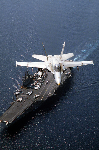 An F/A-18C Hornet aircraft of Strike Fighter Squadron Seventy-Four (VFA-74) in flight over the Aircraft Carrier USS SARATOGA (CV 60) during Operation DESERT SHIELD