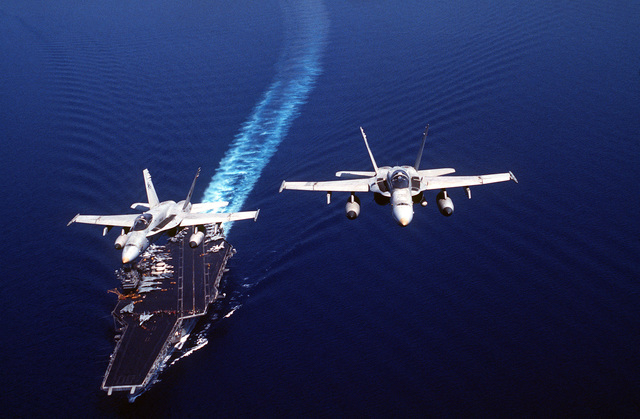 Two F/A-18C Hornet aircraft pass over the Aircraft Carrier USS SARATOGA (CV 60) during Operation DESERT SHIELD. The aircraft are assigned to Strike Fighter Squadron Seventy-Four (VFA-74)
