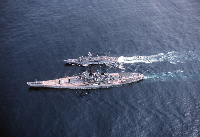 A high angle port view of the battleship USS IOWA (BB 61) refueling the guided missile destroyer USS HALYBURTON (FFG 40) during an underway replenishment. The ships are participating in NATO Exercise OCEAN SAFARI '85