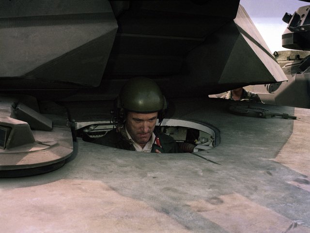 Major General Cooper of the British Royal Armoured Corps sits in the driver's compartment of an M1 Abrams main battle tank during his visit to the US Army Armor Center