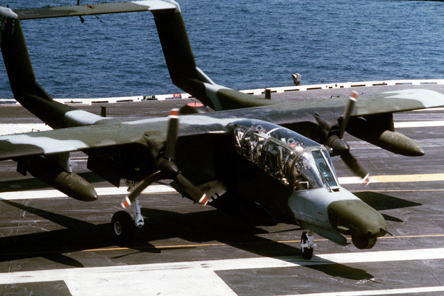 High angle view down at an OV-10D Bronco Observation Aircraft as it taxis clear of the landing zone onboard the Forrestal Class, Aircraft Carrier USS SARATOGA (CV 60). The aircraft is testing flight qualifications off the coast of North Carolina