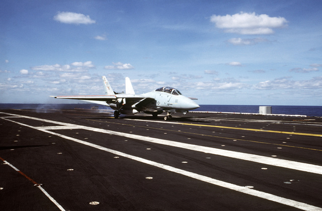 A US Navy F-14A Tomcat fighter aircraft from Squadron Seventy-Four (VF-74) catches the arrester wire after landing onboard the Forrestal Class, Aircraft Carrier USS SARATOGA