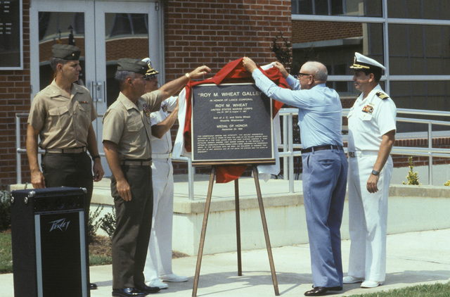 Mr. J.C. Wheat unveils a plaque during a ceremony naming the enlisted dining facility in honor of his son, Lance Corporal (LCPL) Roy M. Wheat, a Medal of Honor recipient. Marine Colonel (COL) Barnum and Navy Captain (CAPT) A.J. Rochells are seen at left