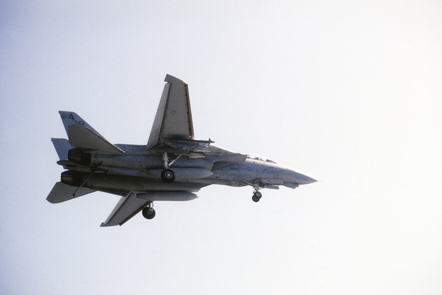 Underside view of a US Navy F-14A Tomcat aircraft from Fighter Squadron Seventy-Four (VF-74)passing over the Aircraft Carrier USS SARATOGA (not shown) after taking a wave-off during flight operations off the coast of Florida. The aircraft has both the landing gear and arrestor hook in the down position in preparation for landing