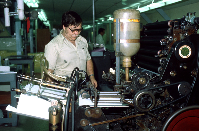Marshall Nace adjusts paper on an offset press in the Field Printing Plant