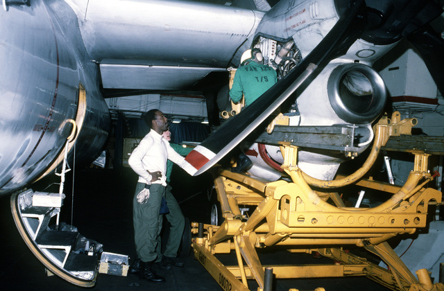 Personnel from the Airborne Early Warning Squadron One-Two-Five (VAW-125) are shown servicing the port engine of an E-2C Hawkeye aircraft on the hangar deck of the Forrestal Class, Aircraft Carrier USS SARATOGA (CV 60)