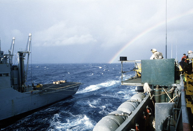The Kilauea Class, Ammunition Ship USS SANTA BARBARA (AE-28), (Left) takes part in an underway replenishment with the Forrestal Class, Aircraft Carrier USS SARATOGA (CV 60) off the coast of Florida. A colorful rainbow is seen in the background