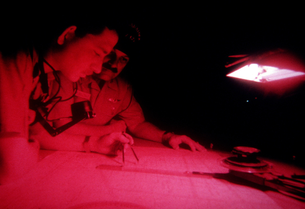 Under the red glow of the night battle lights, men of the ship's navigation department plot the course of the Forrestal Class, Aircraft Carrier USS SARATOGA (CV 60) as the ship operates off the coast of Florida