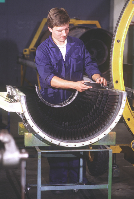 A Belgian aircraft engine mechanic polishes and installa a jet engine blade in the engine shop