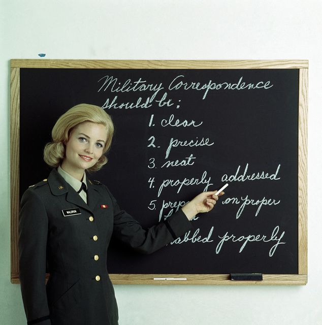 A female US Army officer conducts a class on military correspondence