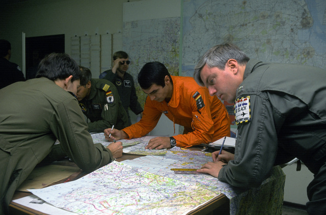Captain (CPT) Jim Marshall and pilots from other countries plot navigational courses during the Tactical leadership Program