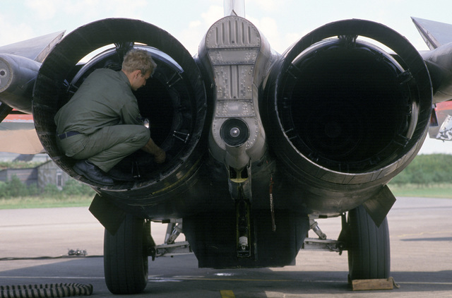 SENIOR AIRMAN (SRA) David Herdrick inspects the exhaust nozzles on the afterburners duct segment of an F-111 aircraft