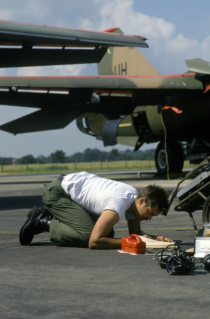 SENIOR AIRMAN (SRA) William Hynson, a crew chief from the 20th Aircraft Generation Squadron, signs the preflight form after inspecting the flaps of an F-111 aircraft