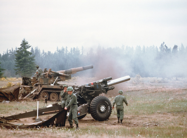 US Army artillery crews conduct a firing exercise with an M114 155 mm howitzer, bottom, and an M110 203 mm self-propelled howitzer
