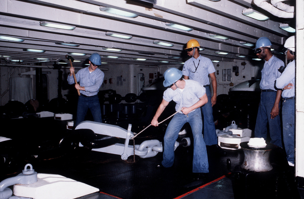 Boatswain mates in the forward windless compartment of the Forrestal Class, Aircraft Carrier USS SARATOGA (CV 60) prepare to let go the anchor as the ship makes a port call in the U.S. Virgin Islands
