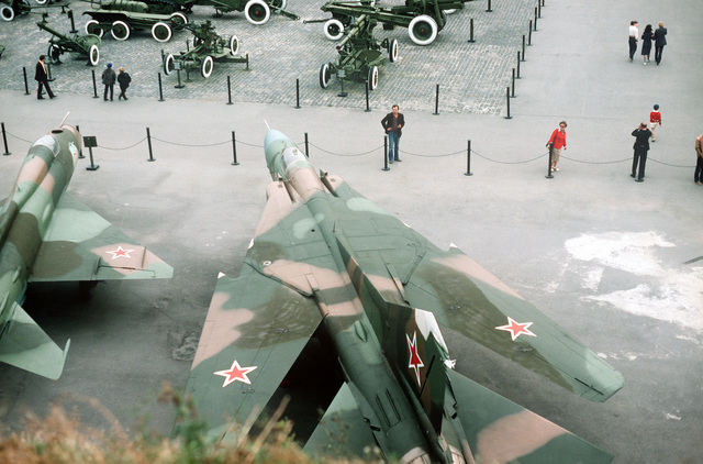 Overhead rear view of a Soviet MiG-23 Flogger B fighter aircraft on public display at the Memorial Complex of the Ukrainian State. A portion of a MiG-21 Fishbed fighter aircraft can be seen to the left. Other assorted military vehicles can be seen in the background